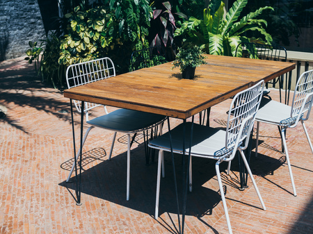 Wooden dining table with white chairs in the outdoor garden on sunny day.