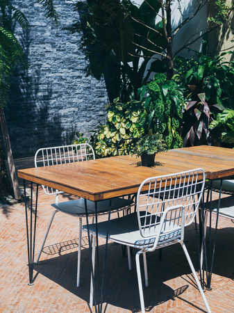 Wooden dining table with white chairs in the outdoor garden on sunny day vertical style.