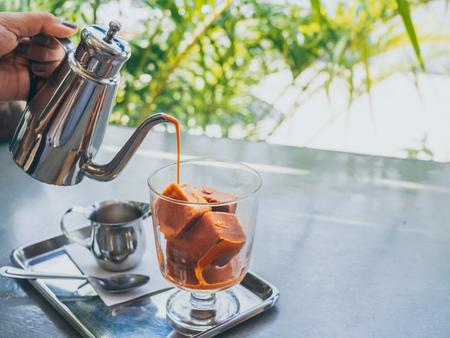 Hand, die thailändischen Milchtee aus Edelstahlkrug auf thailändische Tee-Eiswürfel in Glas mit Milch in kleinem Krug auf Edelstahltablett auf Betontisch mit Kopierraum gießt.
