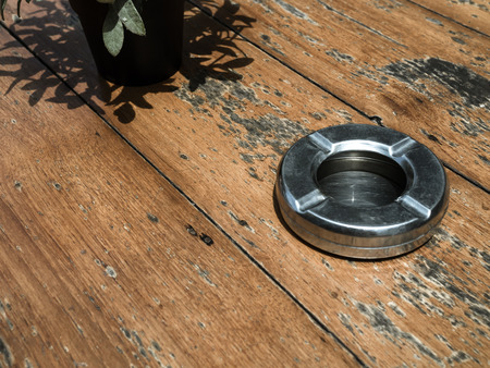 Round steel metal empty ashtray on wooden table with copy space. 版權商用圖片