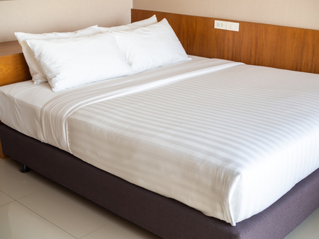 Clean white bedding with four white pillows in hotel bedroom.