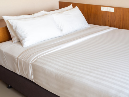 Clean white bedding with four white pillows, white switches, electrical plug on wooden background in hotel bedroom.