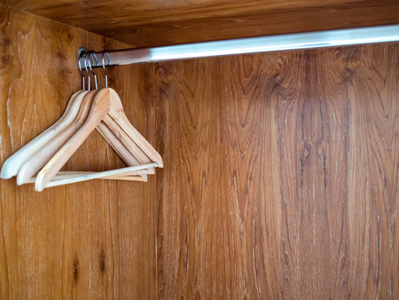 Wooden clothes hangers hanging on stainless steel bar in empty wooden closet with copy space.