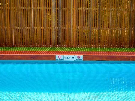 Nessun segno di immersione e segno di profondità della piscina sul bordo della piscina sulla piscina all'aperto su sfondo di recinzione in legno con spazio di copia.