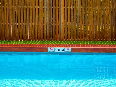 No diving sign and pool depth sign on pool edge on outdoor swimming pool on wooden fence background with copy space.