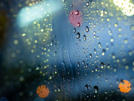 Close-up rain drops texture on car window with colorful bokeh abstract background.