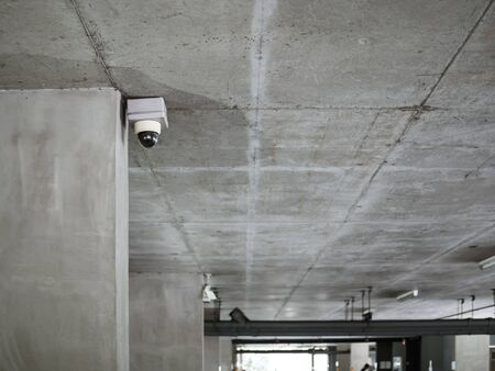 CCTV camera installed on concrete ceiling in the parking lot with copy space.