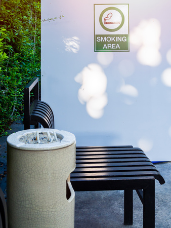 Black chairs with ashtray in smoking area on green garden background. Smoking area sign in smoking zone. Éditoriale