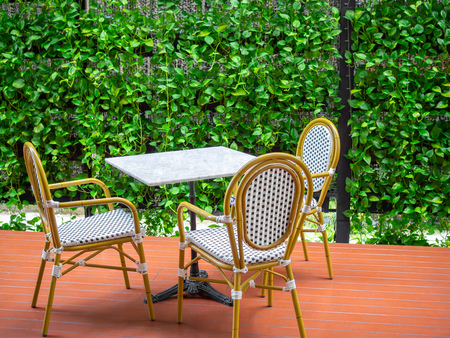 Three wooden white vintage chairs with white marble table on red floor on green ivy plant background. Dining table set in the garden.