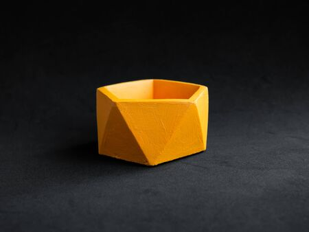 Empty orange pentagon shape concrete planter isolated on dark background. Handmade cement pot for home decoration. Imagens