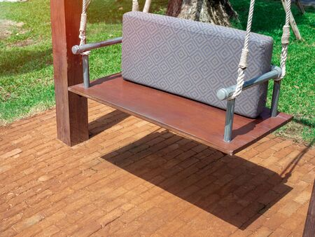 Wooden swing bench with cushion on brick floor and green grass in garden.