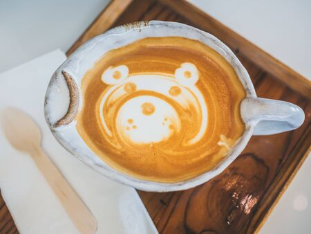 Close-up teddy bear latte art coffee in handmade ceramic cup on wooden tray on white background, top view. Stok Fotoğraf