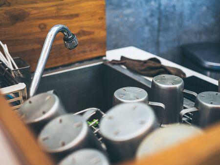 Close-up pile of aluminium mugs on aluminium kitchen sink with faucet in cafe. 版權商用圖片 - 130785924