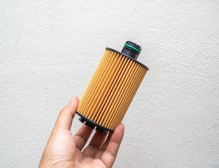 Oil filter. Hand holding car fuel filter isolated on white background.