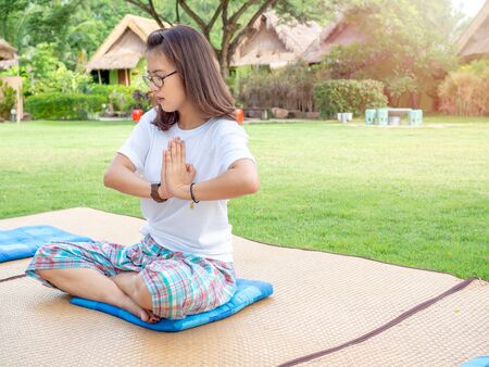 Yoga in park. Asian woman wearing glasses doing yoga, hand exercises outdoor on cushion on mat on the lawn in the morning. Stockfoto