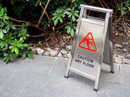 Caution wet floor sign. Metal sign showing warning of caution wet floor on the ground near the garden.