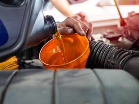 Mechanic hand pouring fresh  engine oil through orange funnel into the car engine at maintenance repair service station. Engine oil change. Stok Fotoğraf