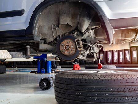 Wheel car waiting for change tires on lifted automobiles at auto service garage.