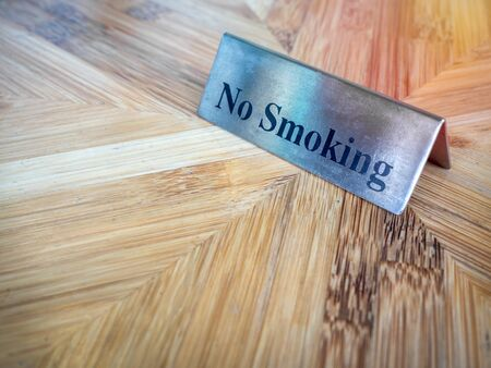 No smoking sign on wooden table. Warning sign, text no smoking  on silver metallic style plate sign. Banco de Imagens