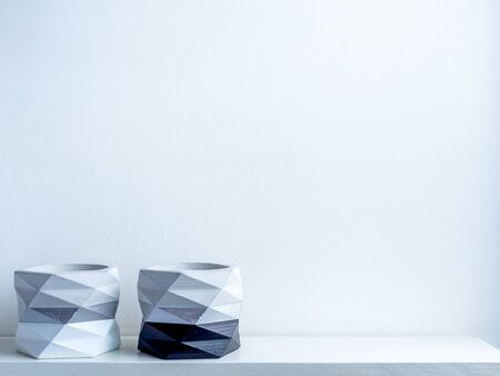 Cactus pot. Beautiful painted concrete pot. two empty modern geometric concrete planters, black and white painted on white wooden shelf on white wall background with copy space.
