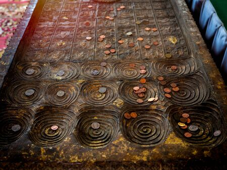 Top view of many coins, Thai baht placed on replica of buddha's footprint in buddhist church in local temple in Thailand. Belief and faith of Buddhism concept.
