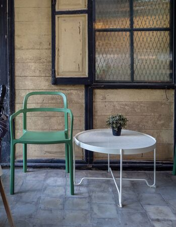 Modern green chair and white round table with green plant in vase decoration near the window in old wooden house background.