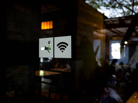 Signs on glass door. No smoking sign, wireless signal icon sign for free wifi on cafe background. Decal sticker signs pasted on front door outside the coffee shop.