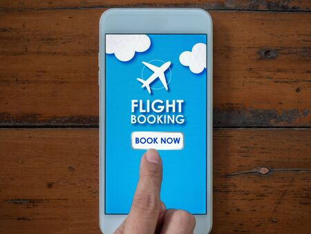 Flight booking online with smartphone. Top view finger touching on mobile phone for buying or booking air flight online airline ticket. Stockfoto