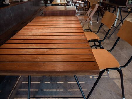 Brown wood plank table with simple wooden chair in cafe loft style. Фото со стока