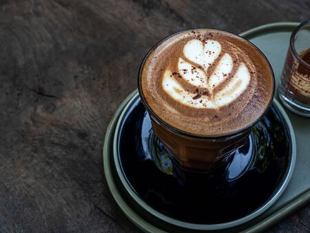 Mocha coffee with latte art in glass on wooden table background, minimal style.