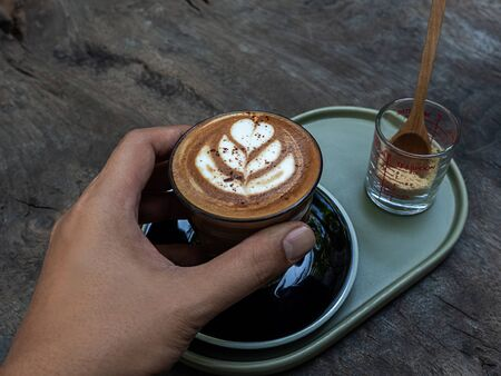 Hand holding mocha coffee with latte art on wooden table background.