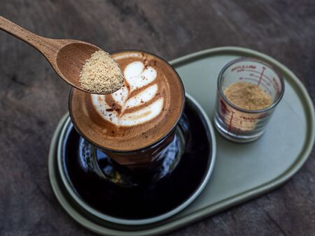 Brown sugar in wooden spoon with mocha coffee with latte art on wooden table background, top view.