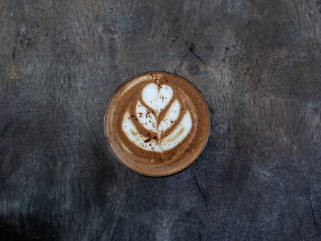 Mocha coffee with latte art in glass on wooden table background, minimal style from top view.
