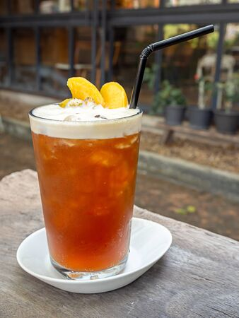 A glass of iced sparkling americano coffee with pieces of fresh orange with drinking straw on wooden table vertical style.