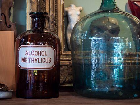 Vintage glass bottle on wooden shelf. Empty danger chemical bottle in science room. Фото со стока