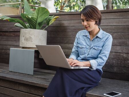 Beautiful happy asian woman wearing blue jeans shirt using laptop computer on her lap near plant pot on wooden wall background.