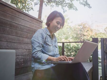 Beautiful happy asian woman wearing blue jeans shirt using laptop computer on her lap on wooden wall background.