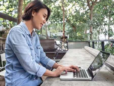 Beautiful happy asian woman short hair wearing blue jeans shirt using laptop computer on concrete table in cafe with green background.