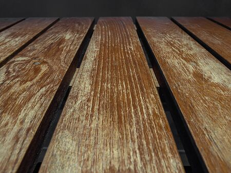 Empty old wooden table top on dark background.