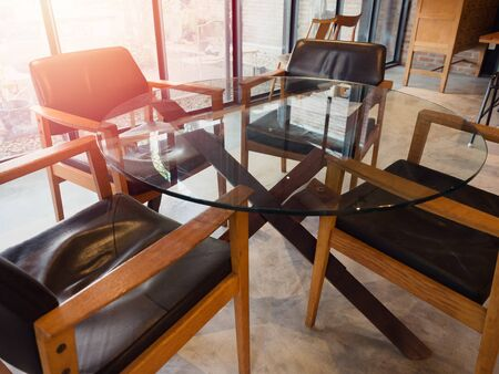 Modern round glass table with four wooden chairs in living room loft style near window glass with sunlight from outside. Фото со стока