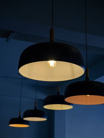 Beautiful round modern ceiling lamps with light bulbs in dark blue room background vertical style.