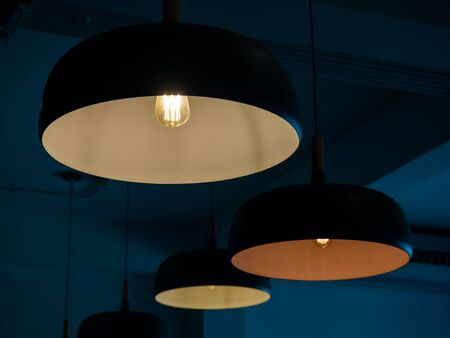 Beautiful round modern ceiling lamps with light bulbs in dark blue room background.