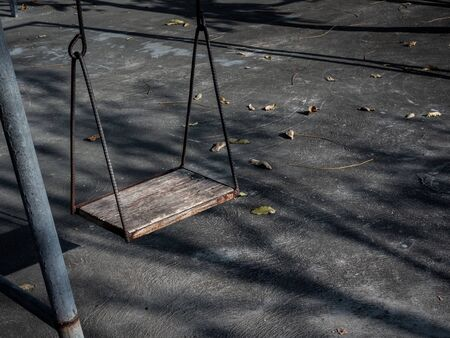 Old lonely wooden swing on sunset time with light and shadow. Vintage wood swing with leaves on the ground with copy space.