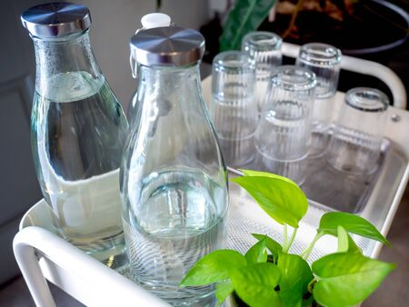 Free drinking water self service set in cafe. Pile of glass in tray and bottles of drinking water on trolley decoration with green plant.