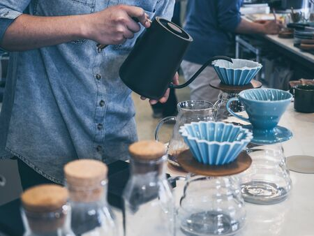 Barista in blue shirt pouring hot water from black kettle into coffee ground with filter on white counter bar in cafe.