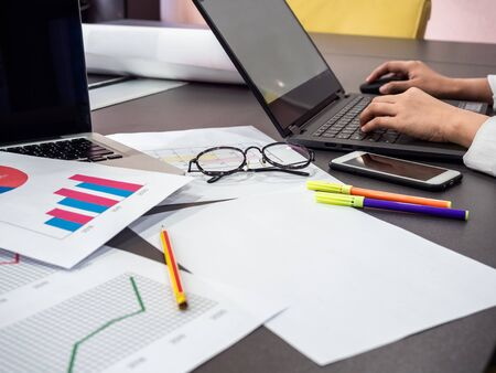 Business goal concept. Business accessory, blank paper, diagrams graphs, smartphone, pencil, glasses, highlighter pen with hands working with laptop computer on table.
