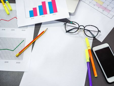Business goal concept. Business accessory, blank paper, diagrams graphs, smarphone, pencil, glasses and highlighter pen on table., top view