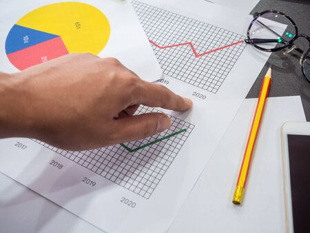Business goal concept. Hand pointing on 2020 on diagrams graphs with business accessory, pencil, smartphone and glasses on table. Фото со стока