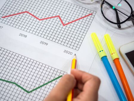 Business goal concept. Close-up hand pointing on 2020 on diagrams graphs by pencil with glasses, smartphone and highlighter pen on table.