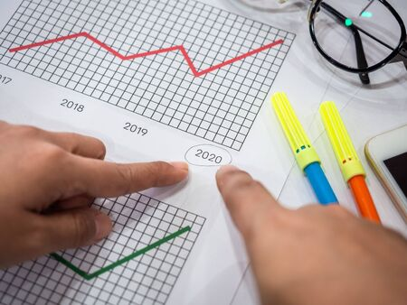 Business goal concept. Close-up hands pointing on 2020 on diagrams graphs with glasses, smartphone and highlighter pen on table.